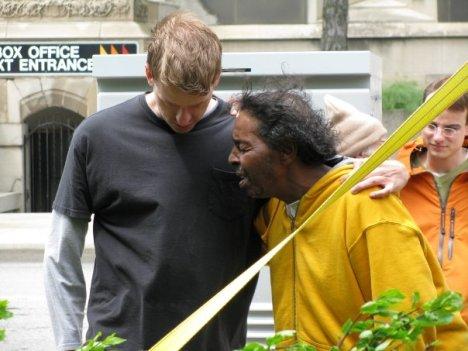 Josh Belcher praying with a man at Cass Park